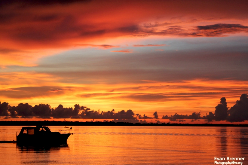 A boat floats by a late-evening sunset on the west coast of Florida.